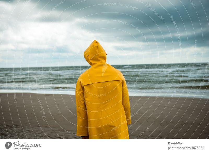 Mann spaziert mit Friesennerz am Strand entlang spazieren friesennerz Unwetter Wetter Wetterumschwung Regenjacke Himmel schlechtes Wetter Gewitterwolken gelb
