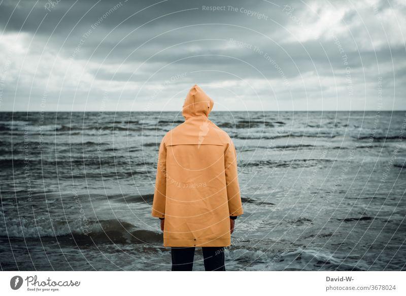 Mann mit Friesennerz am Strand beobachtet das Meer friesennerz beobachten Ozean Wellen dunkel düster alleine verlassen Gefahr Wasser ertrinken Fürsorge Gedanken
