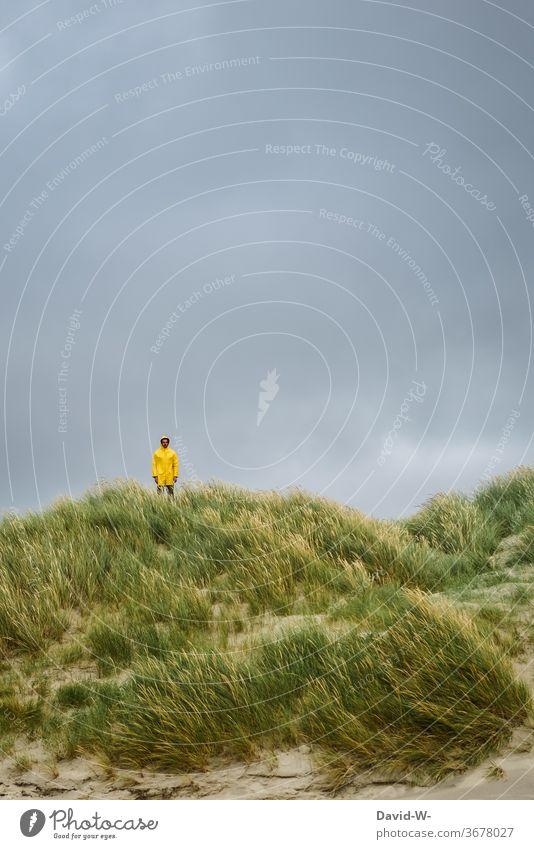 Mann in gelber Regenjacke steht in den Dünen bereit für das gleich eintreffende Unwetter Friesennerz Deich Gewitter nass Regenschauer Urlaub Urlauber Herbst