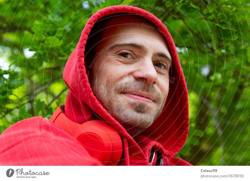 Fröhlicher junger Mann Hintergrund Kopfhörer Kapuzenpulli männlich Porträt Musik Atelier gutaussehend hören Person Erwachsener Typ Menschen attraktiv lässig