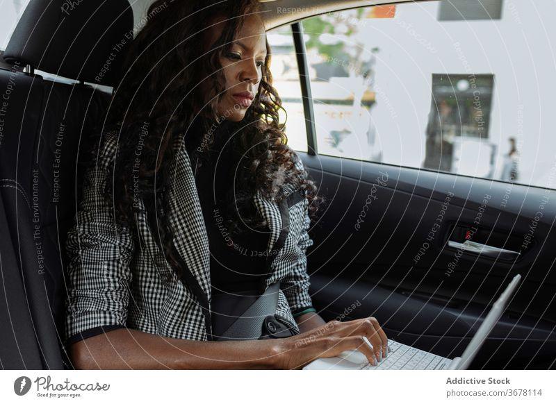 Geschäftsfrau mit Laptop im Auto PKW benutzend Arbeit Frau beschäftigt modern ernst Apparatur jung Afroamerikaner schwarz ethnisch Ausflug urban Gerät