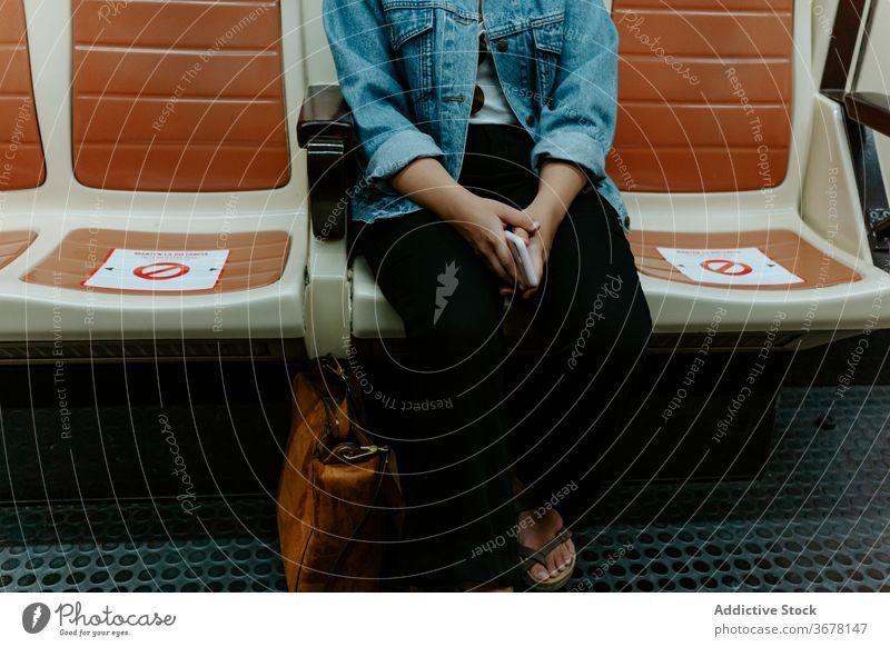 Frau in U-Bahn-Wagen sitzend mit Markierung zum Abstandhalten Coronavirus Passagier soziale Distanzierung COVID Pandemie Einschränkung Infektion Sitz