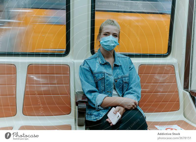 Junge Frau mit Schutzmaske im U-Bahn-Zug Coronavirus Passagier Mundschutz soziale Distanzierung COVID Pandemie Einschränkung Infektion Sitz allein unterirdisch