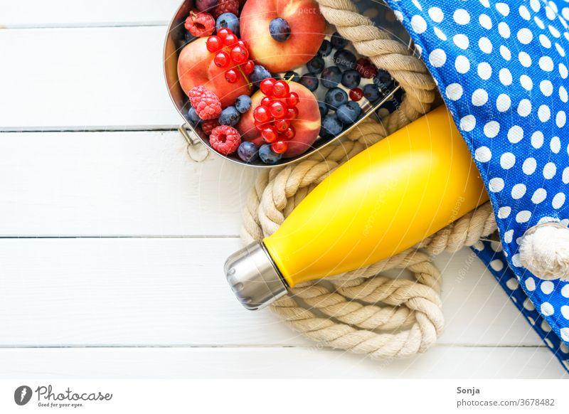 Strandtasche mit einer gelben Wasserflasche und frisches Obst in einer Blechdose. Draufsicht. Badetasche strandurlaub Urlaub Meer Reise Sommerurlaub Farbfoto