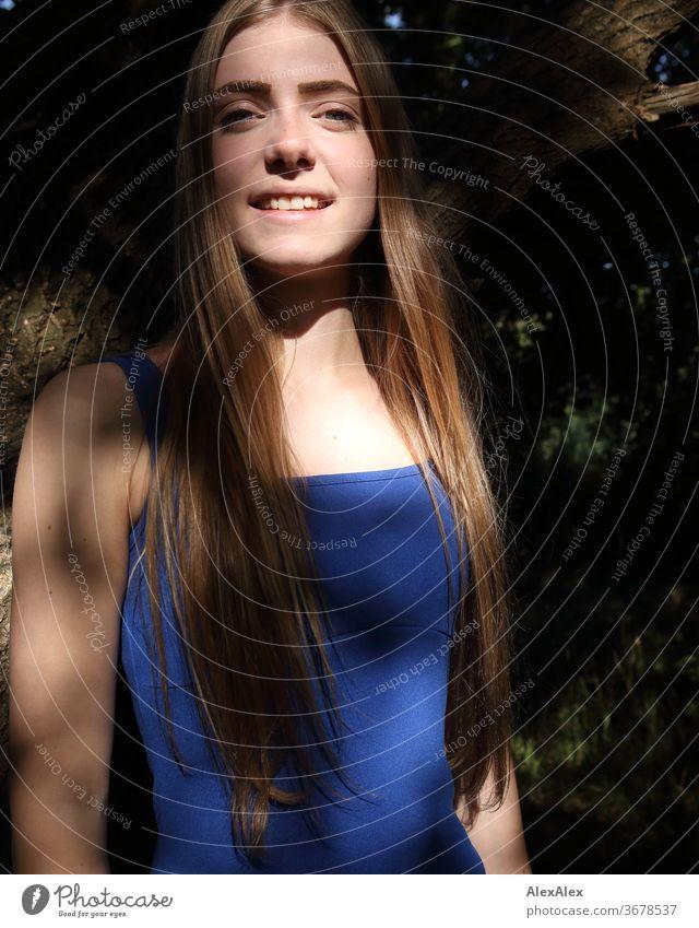Portrait einer jungen Frau in blauem Sommerkleid vor einem Baum mit Schattenspiel Reinheit Glück Schönes Wetter Ausflug Erwartung Sonnenlicht Nahaufnahme Tag