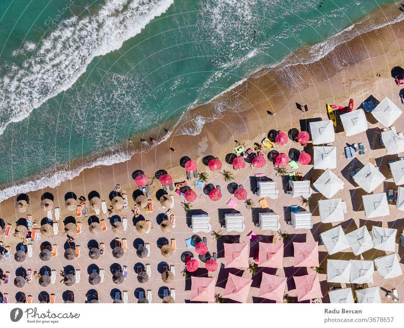 Luftstrand, Menschen und bunte Regenschirme zur Strandfotografie, blaue Meereslandschaft, Meereswellen Antenne Ansicht Sand Hintergrund Wasser MEER Urlaub