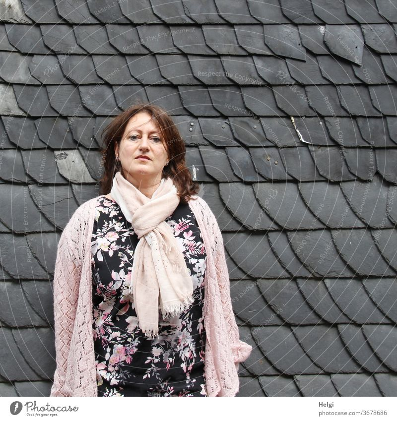 langhaarige Frau im schwarz-rosa-weiß geblümten Kleid und rosa Jacke und Schal steht vor einer grauen Schindelwand Mensch weiblich feminin stehen Wand Schindeln