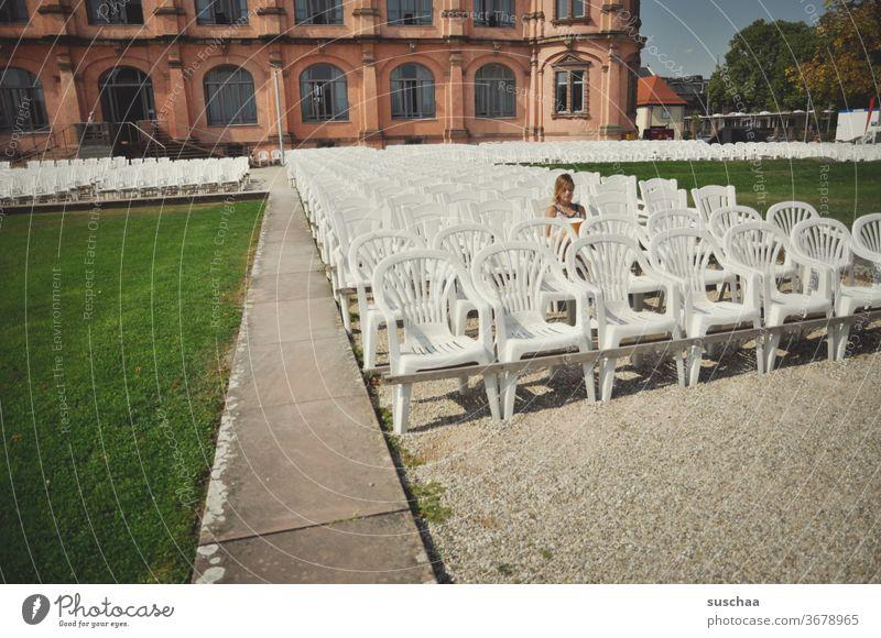 mächen sitzt alleine in einer bestuhlten anlage im freien und wartet darauf, dass die vorstellung beginnt, die aber aufgrund von corona abgesagt wurde Stühle