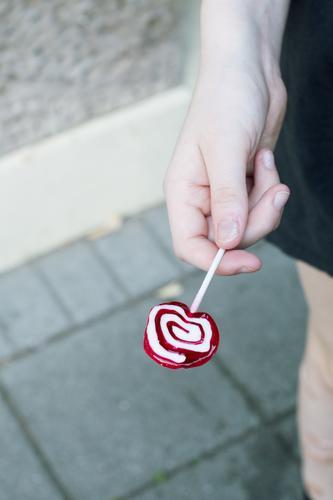 hand, die einen lolly hält Lolly Dauerlutscher Hand Jugendliche Teenager Kind lutschen Süßigkeit Zucker Kindheit süß Xylit zahnfreundlich Zahnarzt Süßwaren