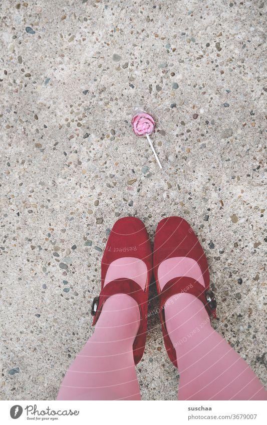 ein lolli auf der straße mit damenfüßen Frau feminin weiblich Schuhe Damenschuhe Damenfüße Strümpfe Lolli Straße Asphalt Beine skurril rosa rot Süßigkeit