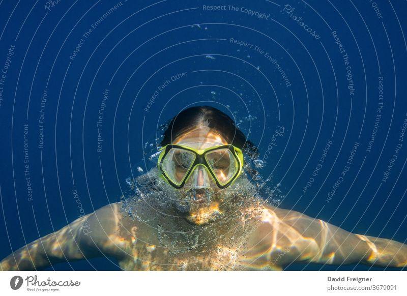 Männlicher Taucher im blauen Wasser. Offenes Meer, Ozean, Schwimmen, aktives Reisen und Unterwasser-Tauchkonzept. Sinkflug frei unter Wasser Mundschutz Mann