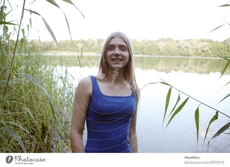 Portrait einer jungen Frau in blauem Sommerkleid in einem See am Ufer Reinheit Glück Schönes Wetter Ausflug Erwartung Sonnenlicht Nahaufnahme Tag