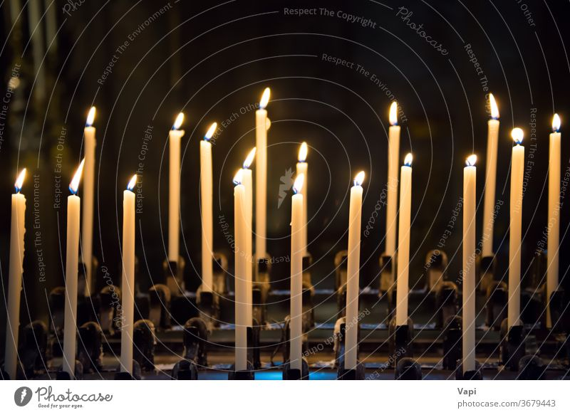 Kerzen in der Kirche candels schwarz blau Hintergrund Licht Kerzenschein Weihnachten Frieden brennend gelb Flamme Wachs dunkel Religion Feuer weiß altehrwürdig
