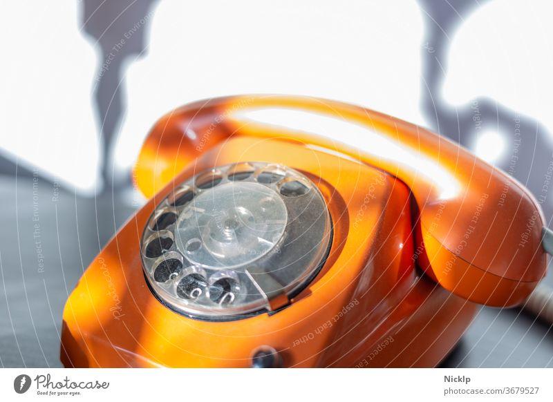 """Telefonieren - orangenes Telefon """"FeTAp 615"""" in orange mit Wählscheibe und Hörer (retro) im hellen Sonnenlicht Wählscheibentelefon Fetap Schnurtelefon"""