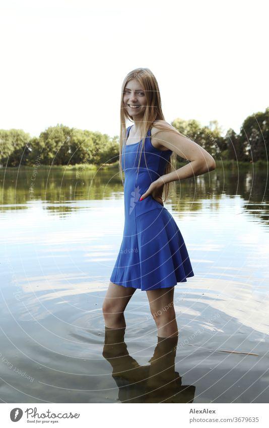 Portrait einer jungen Frau in blauem Sommerkleid in einem flachen See am Ufer Reinheit Glück Schönes Wetter Ausflug Erwartung Sonnenlicht Nahaufnahme Tag