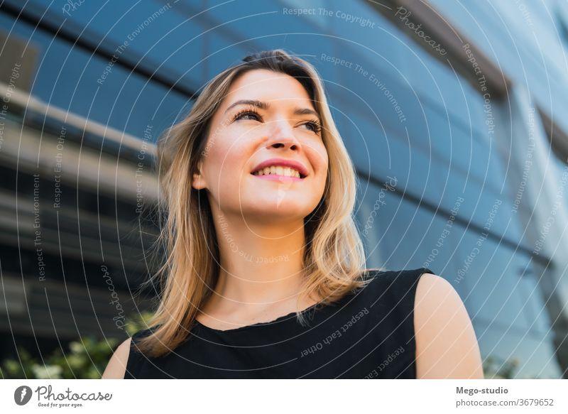 Geschäftsfrau, die vor Bürogebäuden steht. Porträt professionell jung Geschäftsleute korporativ Manager Hinweis Karriere Blick attraktiv Halt Stehen formal