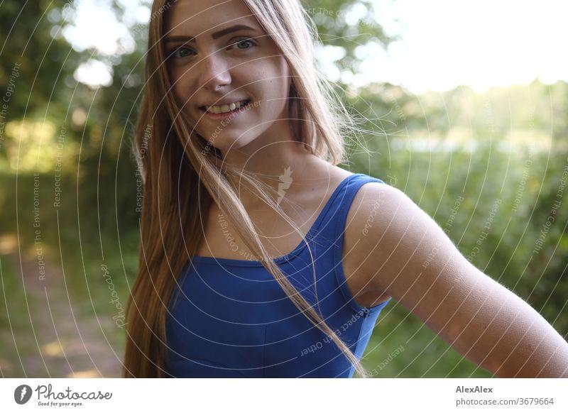 Seitliches Portrait einer jungen Frau in blauem Sommerkleid in der Natur Reinheit Glück Schönes Wetter Ausflug Erwartung Sonnenlicht Nahaufnahme Tag