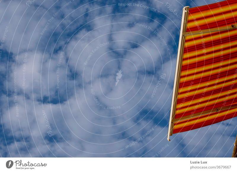 Sommerglühen oder eine Markise leuchtend rot, gelb und orange gestreift vor blauem Himmel mit Schäfchenwolken sommerlich Blauer Himmel Wolkenhimmel Sonnenschein