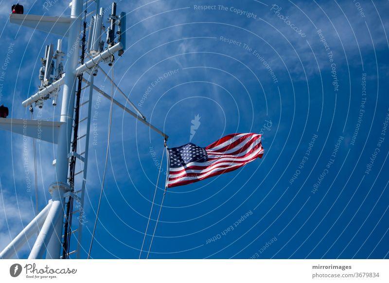 Die Flagge der Vereinigten Staaten von Amerika weht im Wind auf dem Deck eines großen Schiffes auf See mit Mobilfunkmasten amerika Amerikaner Transparente