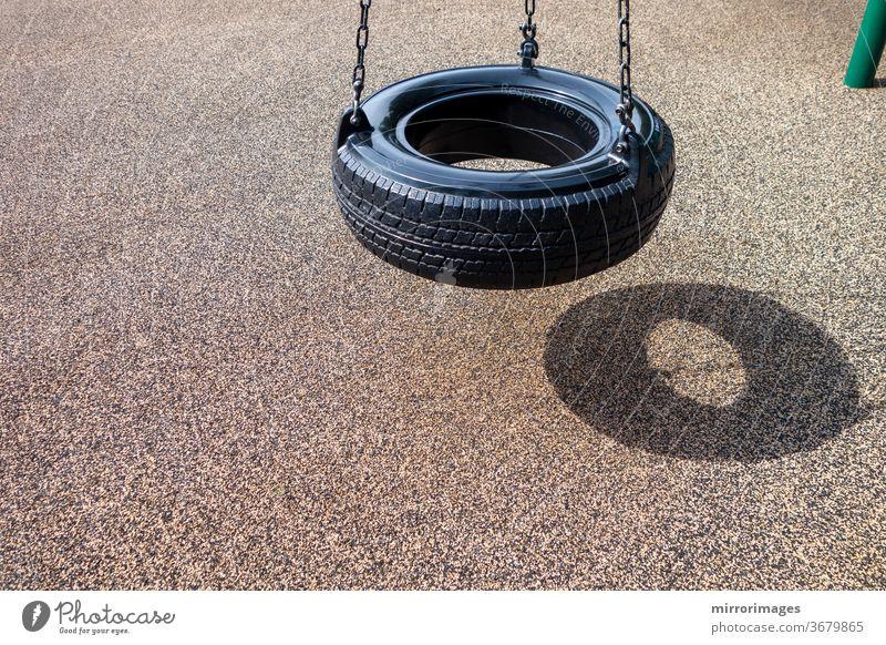 schwarze Kette Reifenschaukel auf einem Kinderspielplatz keine Menschen Aktivität Hintergrund Schwarze Kette Reifenschaukel Ketten Kindheit Kinder schaukeln