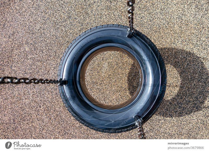 Draufsicht auf eine schwarze Kette Reifenschaukel auf einem Kinderspielplatz keine Menschen Aktivität Hintergrund Schwarze Kette Reifenschaukel Ketten Kindheit