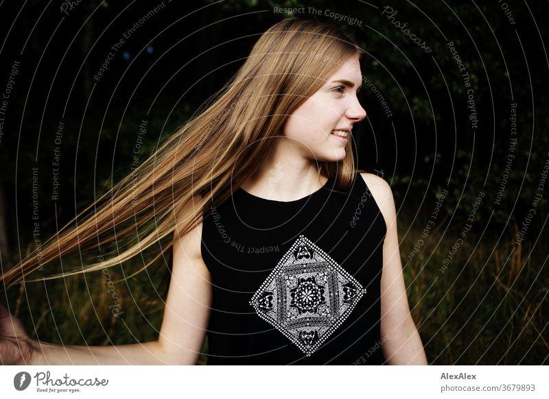 Seitliches Portrait einer jungen Frau in der Natur vor einem Wald, die ihre Haare ausbreitet Reinheit Glück Schönes Wetter Ausflug Erwartung Sonnenlicht