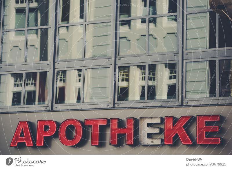 kaputter Schriftzug - Apotheke schriftzug defekt Wort Haus Gebäude Fenster Spiegelung leuchten Buchstaben Menschenleer Außenaufnahme Farbfoto Wand Text Fassade