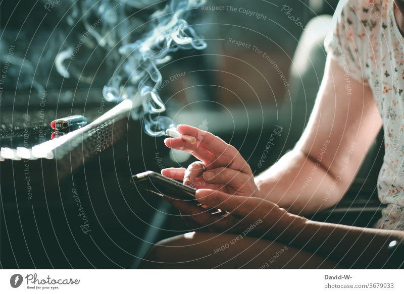 Frau mit Zigarette in der Hand tippt auf ihrem Handy herum Tippen Hände Finger rauchen Rauch Qualm Sucht Suchtverhalten suchtgefahr ungesund Alltagsleben Leben