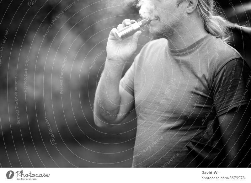 Mann zieht an einer E-Zigarette e-zigarette Zigarrete elektrisch elektronisch Abhängigkeit Drogen sucht suchtpotential süchtig abhängig sein Schwarzweißfoto