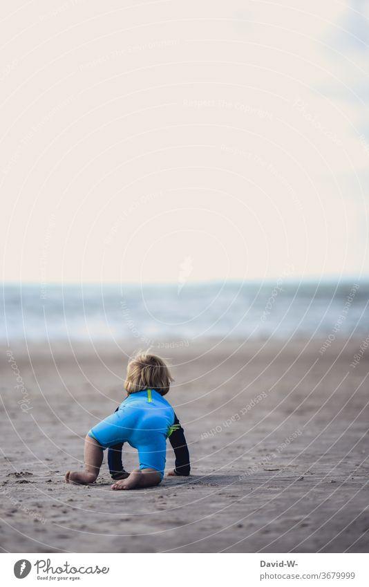 kleiner Junge fühlt sich vom Meer magisch angezogen Kind Kleinkind betrachten betrachtend beeindruckt Ozean Wellen Urlaub Strand alleine schauen denken Gedanken