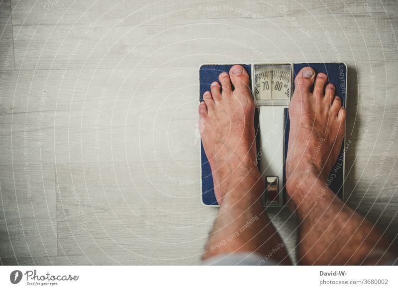 auf der Waage stehen und das Gewicht ablesen Mann steht wiegen Gesundheit retro alt Ernährung Messinstrument messen gewichtskontrolle ermitteln Kilogramm