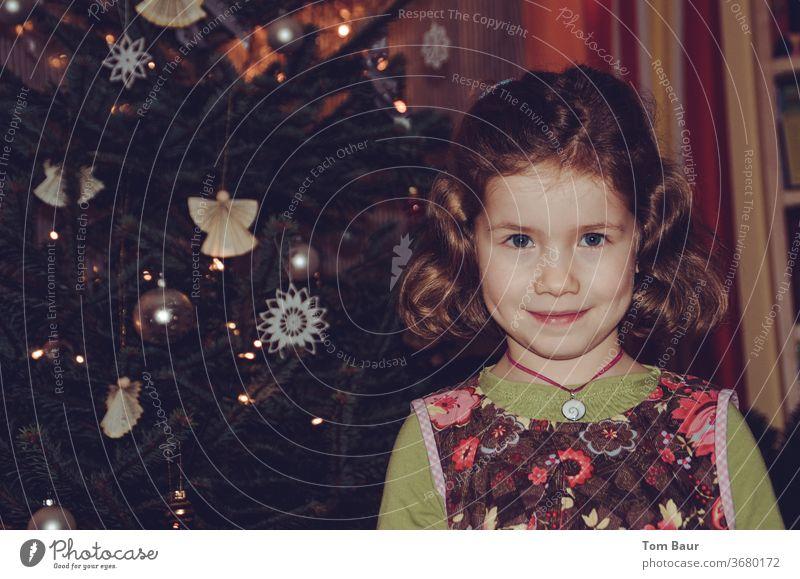 Portrait eines Mädchens vor dem Weihnachtsbaum weihnachtsbaum portät Engel christbaum blondes haar Blick in die Kamera fröhlich Fröhlichkeit festlich