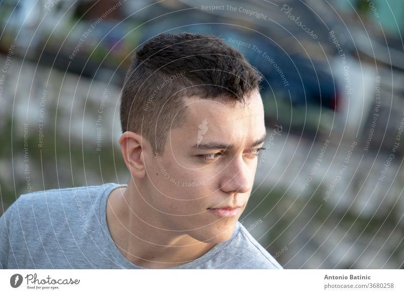 Junger erwachsener Mann sitzt ruhig da und blickt mit besorgtem Blick in die Ferne. Kopfschuss schließen Mode selbstbewusst träumend tausendjährig 20s lässig
