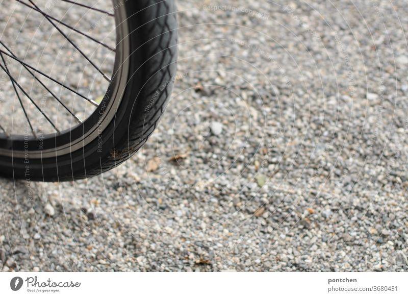 Teil eines Fahrradreifens auf Kies. Mobilität fahrradreifen verkehrswende kies mobilität umweltschutz speichen sport monochrom draußen Fahrradfahren