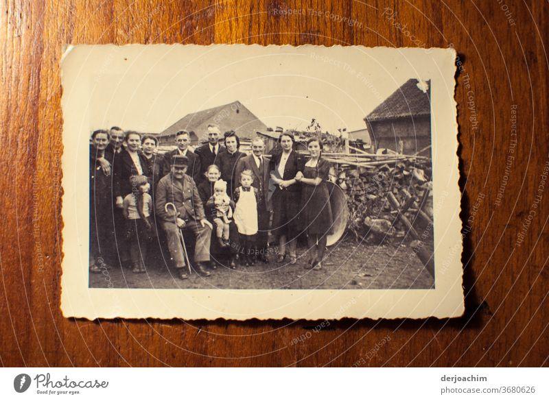 Familien Foto auf dem Lande. Alle stehen  um den Großvater , und Großmutter herum. Im Hintergrund ein Holzstoß . Ganz alte Aufnahme der Familie auf dem Land. Ostpreußische Impressionen