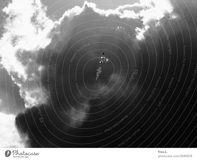 Vor aufgetürmten dunklen Wolken glitzern Kampfjets im Sonnenlicht. Flugzeuge Himmel Luftwaffe Schauflug Formationsflug Krieg Militär