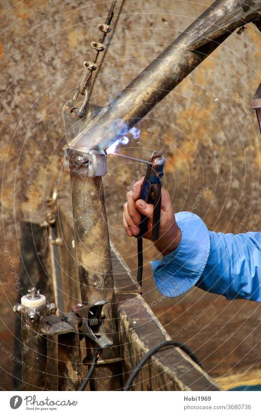 Anschweißen eines Metallbügels an einen Rahmen mit Elektroscheißen Schweißen anschweißen elektroschweißen Arbeit Schweißer Industrie gewerblich Gewerbe Eisen