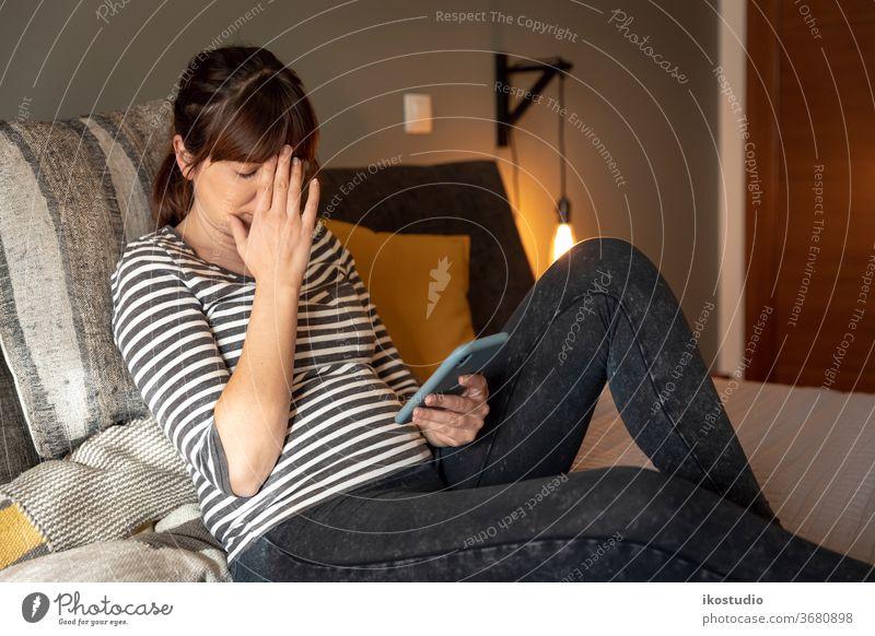 Traurige Frau zu Hause Ärger drücken traurig Smartphone Bett Mitteilung müde depressiont Problematik frustrierter Benutzer erschöpfte Menschen ängstliche Person