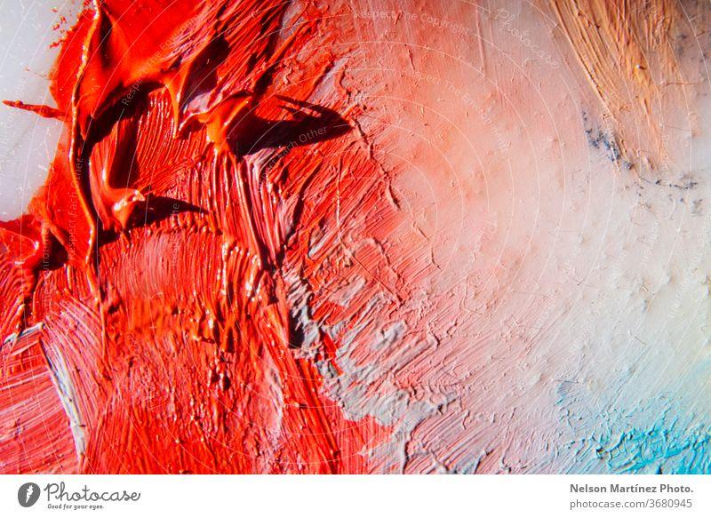 Nahaufnahme einer Farbpalette eines Malers. Farben Rot, Orange, Weiß und Blau. Nahaufnahme der roten Farbe vermischt mit weißer Farbe auf der Leinwand.