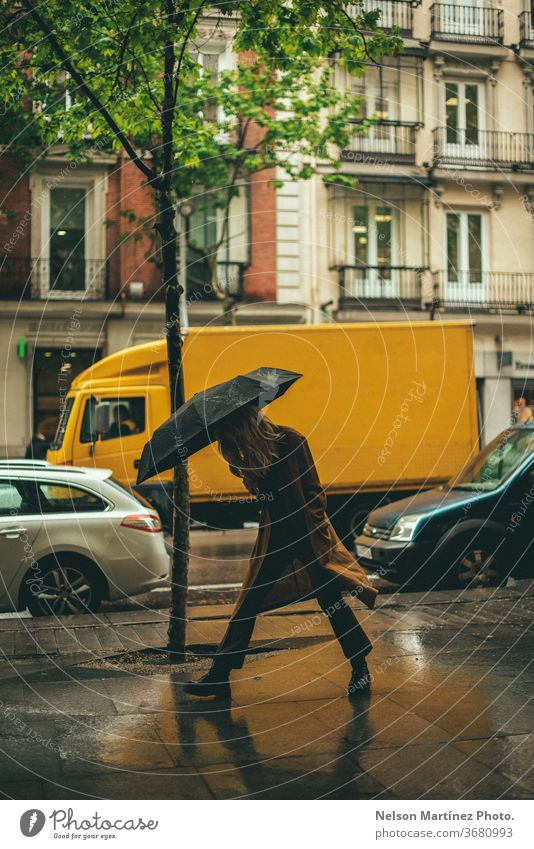 Stilvolle blonde Frau, die im Regen spazieren geht. Sie hält einen schwarzen Regenschirm in einem nicht gesperrten Bereich. regenreich Wetter nass Mensch