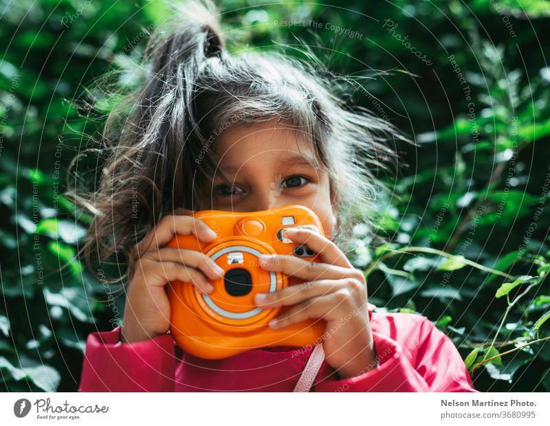Kleines hispanisches Mädchen mit einer orangefarbenen Instax-Kamera in der Hand. Klassische Kamera. Sie steht vor einem grünen Hintergrund. Kind kleines Mädchen