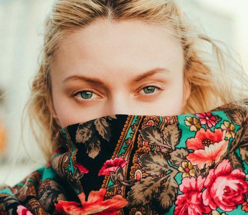 Porträt einer kausalen Blondine.  Sie blickt direkt in die Kamera, die mit einem Schal mit Blumenmuster bedeckt ist. blond Kaukasier Frau schön hübsch Gesicht