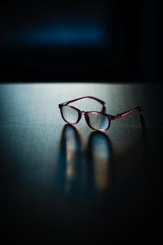 eine Brille liegt auf dem Tisch wissen liegen Spiegelung spiegeln Schatten kurzsichtig alter Bild erblinden Lesehilfe Brillenträger liegend Licht
