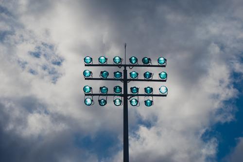 """Licht aus """" Spot"""" an. Leuchtmast mit dunklem Hintergrund, Wolken . Der Mast ist eingeschaltet. Licht & Schatten Architektur blau Außenaufnahme Farbfoto Himmel"""