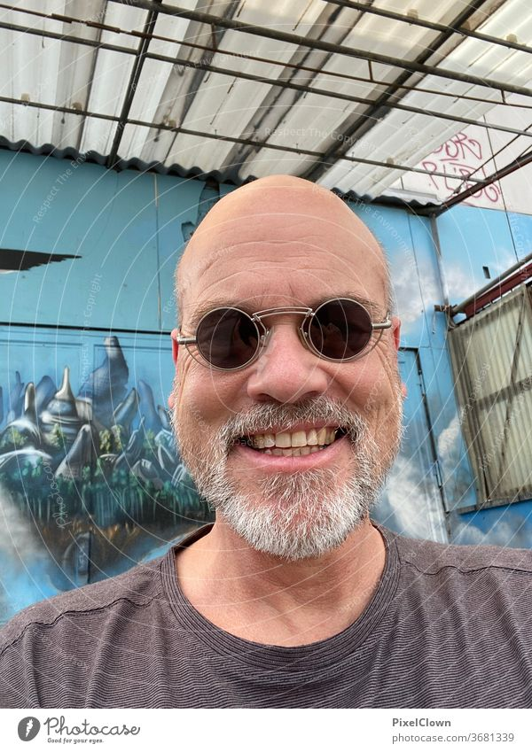 alter Mann in blau Ein Mann allein Porträt Erwachsene Sonnenbrille glatze Gesicht Graffiti Wand Fassade Bart lachen