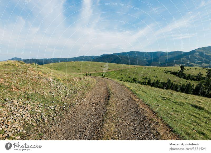 Unbefestigte Straße in den Bergen an einem sonnigen Tag Hintergrund schön blau Wolken Land Landschaft Schmutz Umwelt erkundend Feld Gras grün wandern Hügel
