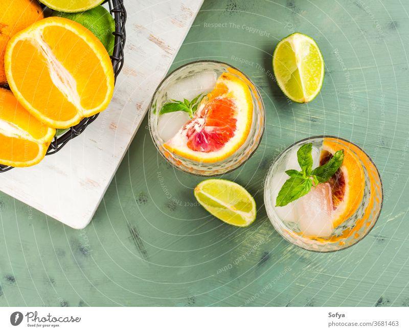 Frisches Sommer-Zitrusgetränk mit Eis auf Grün trinken Zitrusfrüchte Wasser Cocktail Limonade Entzug Mocktail Blutorange Frucht flache Verlegung Draufsicht Kalk