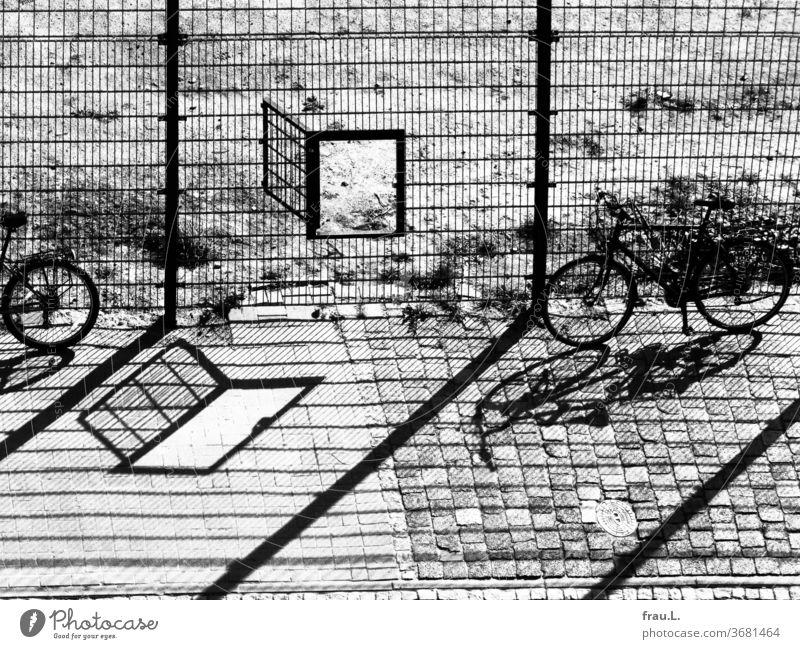 Der gepflasterte Weg staunte nicht schlecht über die Verdoppelung seiner Welt. Schatten Zaun Fahrrad Tür Tor Fußballplatz Pflastersteine Sonnenlicht
