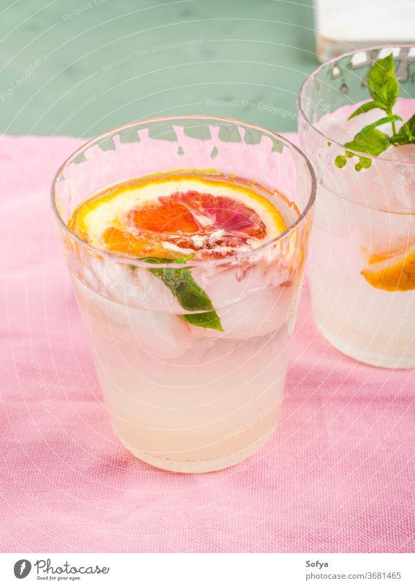 Sommerliches geeistes Zitrusgetränk mit Minze auf rosa Serviette trinken Zitrusfrüchte Wasser Cocktail Limonade aufgegossen Entzug Blutorange Kalk Frucht Saft
