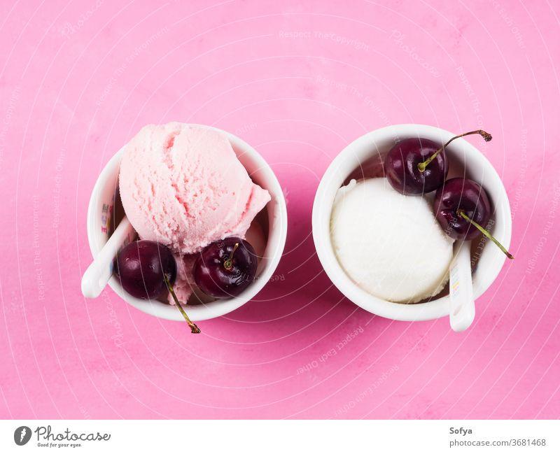 Zwei Eisbecher mit Kirschen auf rosa Erdbeeren Speiseeis Baggerlöffel Ball gelato rot Beeren Joghurt Sommer süß Tasse Sahne Frucht Versuchung Belag Lebensmittel